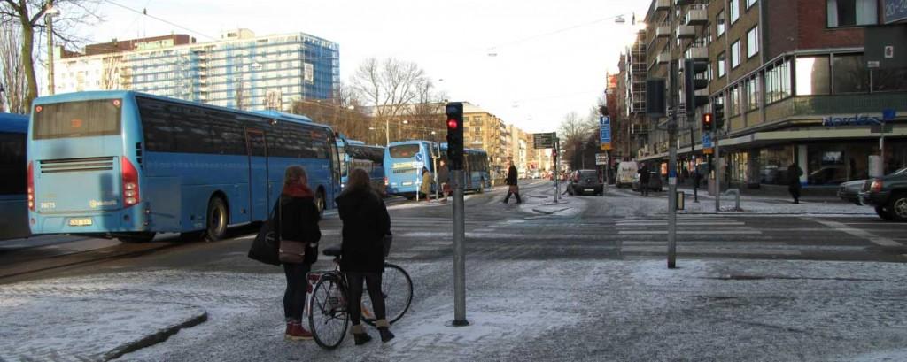 Bussar strömhoppar förbi cykelrött