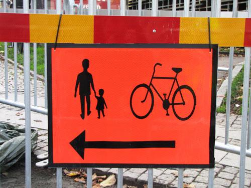 Orange J2-skylt Pil för gående och cyklister