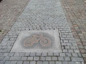 Kopparfärgade cykelsymboler på Fontänbron