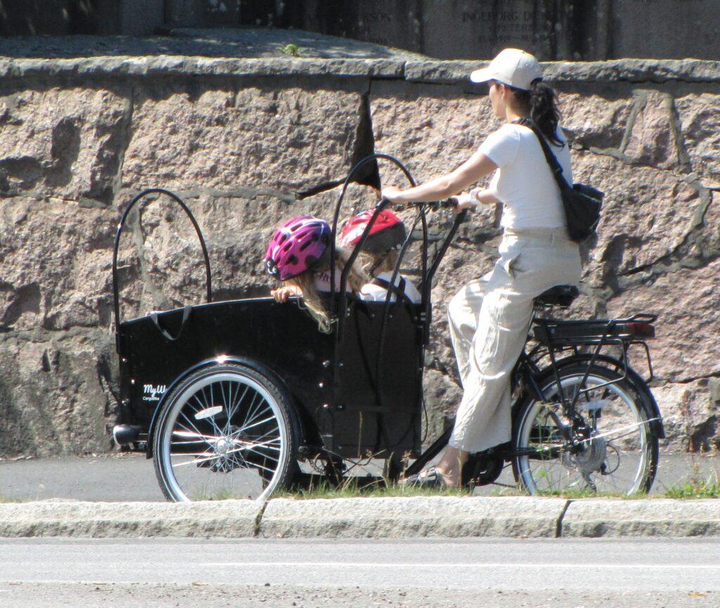 Mor med två barn i lastcykel